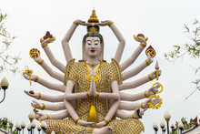 Ko Samui Island, Thailand - March 18, 2019: Wat Laem Suwannaram Chinese Buddhist Temple. Closeup Of Giant Guan Yin Goddess Statue With 18 Arms, Nothing Else, Against Silver Sky, Broken Foliage And Lan