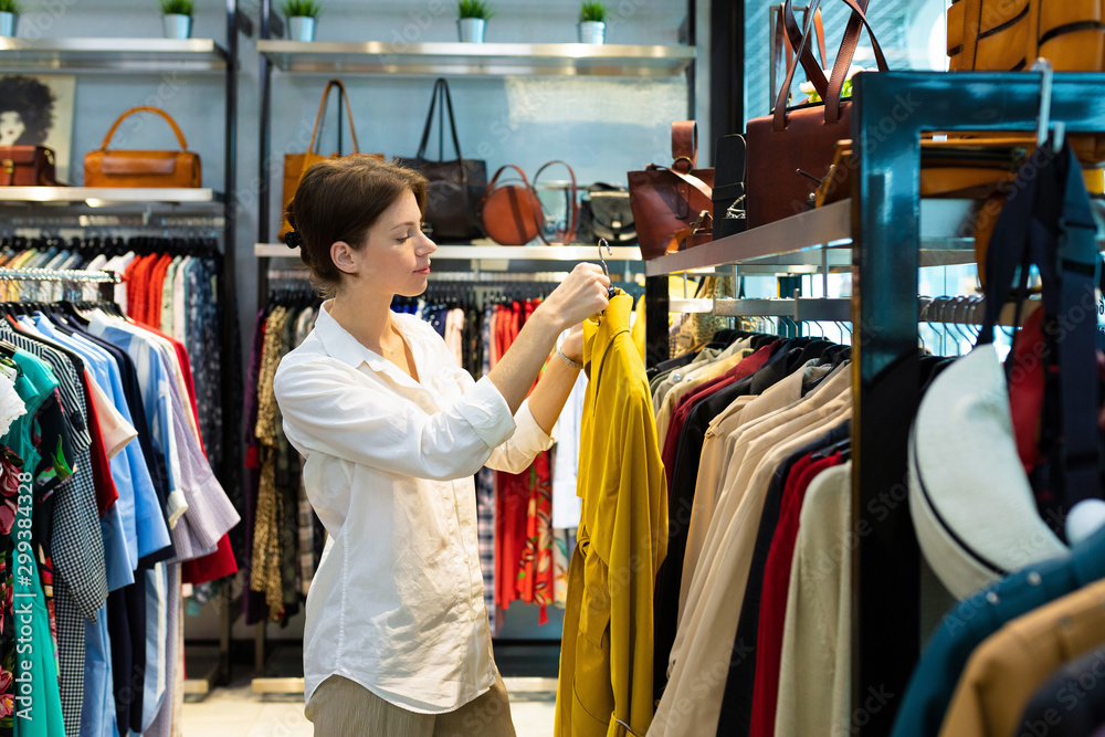 Fototapeta Young woman is choosing raincoat in clothing shop and holding one raincoat of mustard color