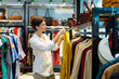 Leinwanddruck Bild - Young woman is choosing raincoat in clothing shop and holding one raincoat of mustard color