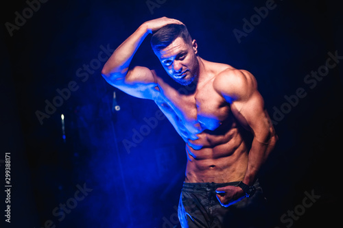 Bodybuilder showing belly and biceps muscles, personal fitness trainer Fototapet