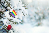 Fototapeta Tęcza - Christmas LGBT. Xmas tree covered with snow, decorations and rainbow flag. Snowy forest background in winter. Christmas greeting card.
