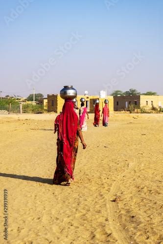 Indian ladies carrying a water bucket near Thar desert. Fototapet