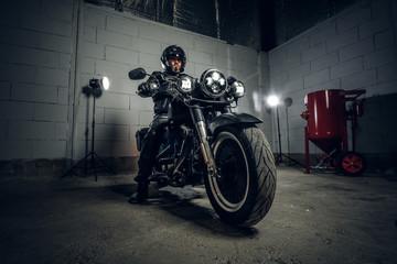 U mračnoj garaži bradati motorista na motociklu pozira fotografu na svom biciklu.