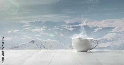 Montage in der Fensternische Dunkelgrau Single tea or coffee cup and landscape of mountains on background. Cup of hot drink with snowly look and cloudly sky in front of it. Warm in winter day, holidays, travel, New Year and Christmas time.