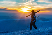 Skier With Ski Is Walking On Sunset