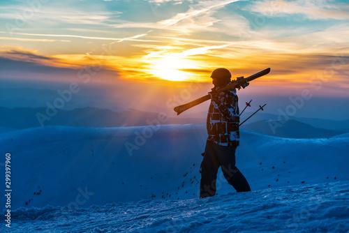 Cuadros en Lienzo skier with ski is walking on sunset