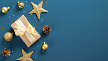 Christmas Blue Background With A Border Of Gift Box, Golden Stars And Balls, Confetti. Flat Lay, Top View, Copy Space. Xmas Banner Mockup, Vintage Postcard Template