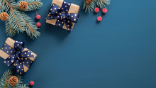 Christmas Tree Branch With Red Berries And Gift Box Over Blue Xmas Background. Flat Lay, Top View, Copy Space. Christmas Banner Mockup With Copy Space