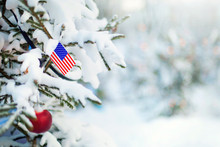 Christmas United States. Xmas Tree Covered With Snow, Decorations And A Flag Of USA. Snowy Forest Background In Winter. Christmas Greeting Card.