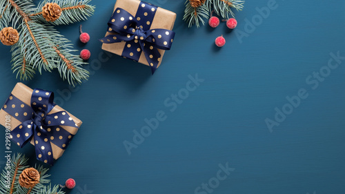 Fotomural  Christmas tree branch with red berries and gift box over blue xmas background