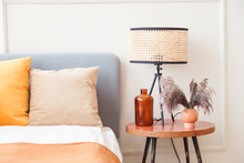 Stylish Lamp On Wooden Nightstand Next To Flower In Big Glass Vase In Scandinavian Bedroom Interior