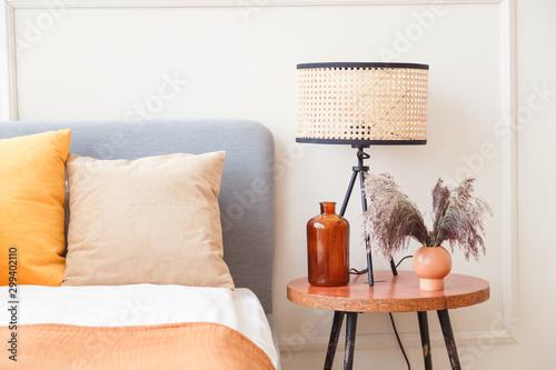 Stylowa lampa na drewnianej szafce nocnej obok kwiatu w dużym szklanym wazonie w skandynawskim wnętrzu sypialni
