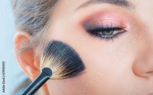 Makeup artist applying makeup on her face using powder brush Canvas Print
