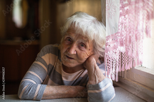 Elderly woman sits sadly near the window at his home.