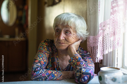 Elderly woman sitting at a table in the house.