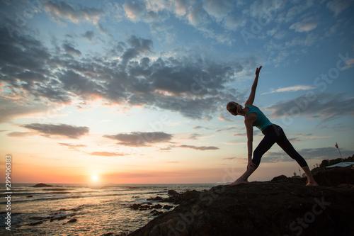 Yoga female sees off the sun on the ocean coast. Exercises.