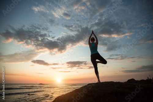 Foto op Canvas Ontspanning Yoga woman sees off the sun on the ocean coast. Exercises.