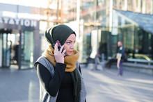 Woman Wearing Headscarf Talking On Phone In City