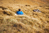 Autumn in mountains. Man himself sitting and resting in high yellow grass on a large mountain slope. Grass growing on hill turns yellow and takes on  colors of autumn. Alpine autumnal scenery.
