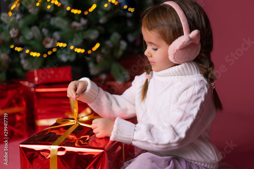 Photo Beautiful little girl in the hat sitting near presents and christmas tree