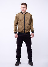 Young Man In Jeans, Shiny Nylon Gold Bomber Jacket On White Background.