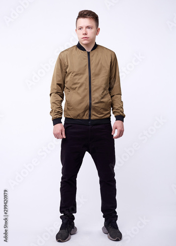 Carta da parati Young man in jeans, shiny nylon gold bomber jacket on white background