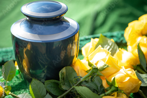 Foto Urn with yellow roses, at an outdoor funeral with space for text
