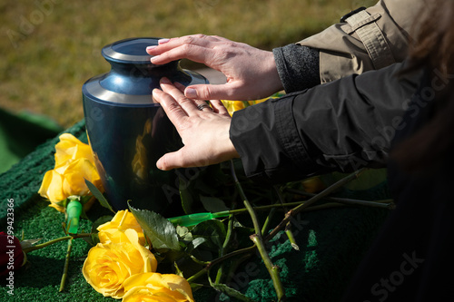 Two hands touching a cremation urn at a funeral Canvas Print