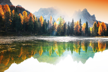 Obraz na SzkleLake with reflection of mountains at sunrise in autumn in Dolomites, Italy. Landscape with Antorno lake, blue fog over the water, trees with orange leaves and high rocks in fall. Colorful forest