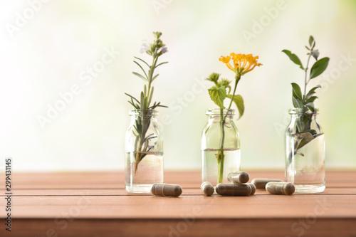 Natural herbal medicine capsules on wooden table with tree jars Fototapeta