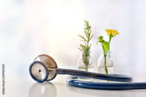 Vials with plants inside and stethoscope natural medicine concept Canvas Print