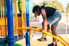 A Young Girl Climbing A Ladder On A Jungle Gym And Developing Her Sense Of Balance.