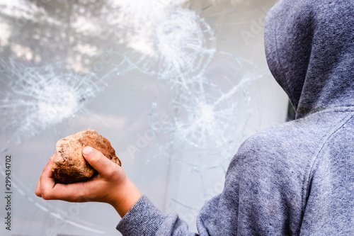 Child holds a stone to throw it against a glass and break a window Fotobehang