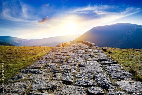 Obraz na płótnie Mountain path uphill to the sky at sunset