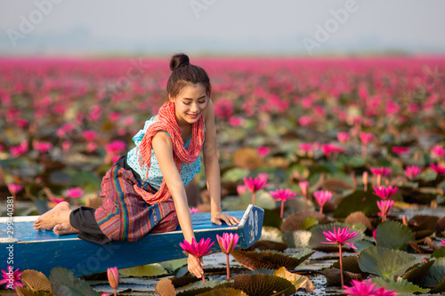 Fotomural Woman on a boat in the lake red Lotus,Beautiful women in Lotus Gardens