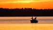 canvas print picture - Silhouette of father and son fishing on a beautiful lake at sunset in northern Minnesota.