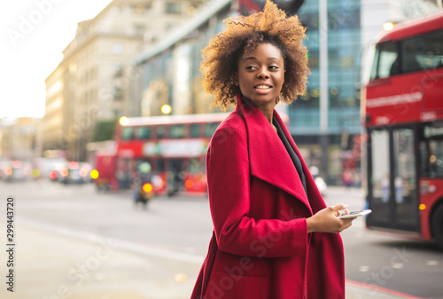 Business woman wearing a red coat, walking in the street