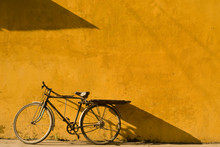 Bicycle Leaning On Yellow Wall...