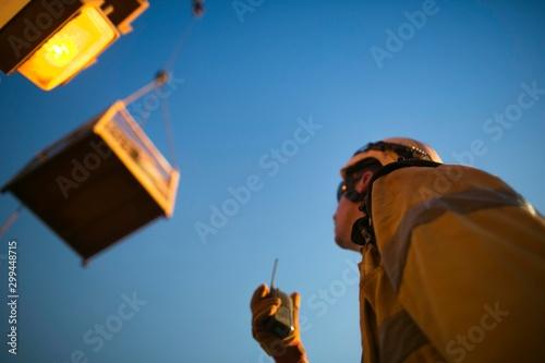 Fotografie, Obraz Defocused picture of rigger crane operator miner wearing helmet, using two way s