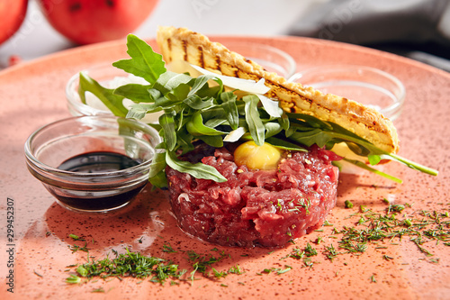 Poster de jardin Echelle de hauteur Steak Tartare Made from Raw Ground Beef with Greens Close Up