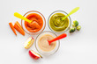 Baby food. Colorful puree in glass jars near vegetables and fruits on white background top view