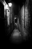 Fototapeta Uliczki - A dark creepy narrow European alley at night, surrounded by bricks and cobblestone. Illuminated only with some street lamps. Concept of scared or being alone and frightened