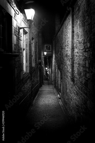 Fototapeta A dark creepy narrow European alley at night, surrounded by bricks and cobblestone. Illuminated only with some street lamps. Concept of scared or being alone and frightened obraz
