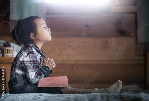 Pinturas sobre lienzo  asian little girl reading and praying on Bible in morning at home