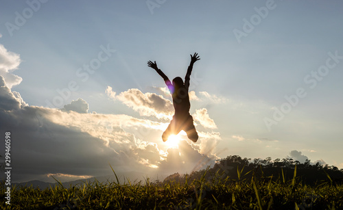 Carta da parati  Silhouette of happy child jumping playing on mountain at sunset or sunrise