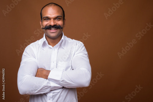 Obraz Portrait of happy Indian businessman with mustache in casual clothing - fototapety do salonu