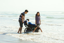 Little Disabled Boy In Wheelchair With Family Walking Along Beach