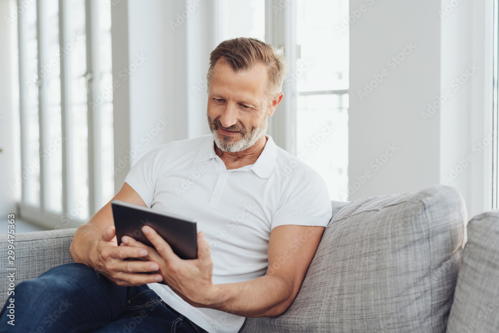 Fototapety, obrazy: Man relaxing at home with his tablet pc