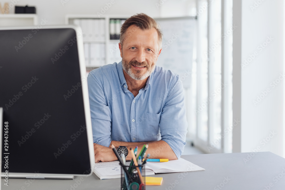 Fototapeta Attentive serious businessman staring at camera