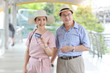 asian traveler couple husband and wife in pink and blue shirt with white nice hat and luggage walking in downtown with happy smiling face while showing credit card for shopping during retirement age